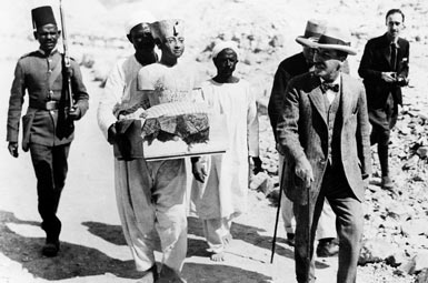 Говард Картер выходит из гробницы в сопровождении работников со статуей Тутанхамона.